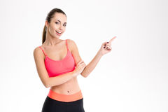 Positive happy young sportswoman pointing away and looking camera Stock Photography
