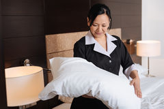 Positive hard working hotel maid looking at the pillow. Professional room service. Positive hard working nice hotel maid looking at the pillow and smiling while Stock Images