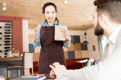 Positive Hispanic waitress working with client. Cheerful content beautiful young Hispanic waitress in apron holding sketchpad gesturing while explaining dish and Royalty Free Stock Image