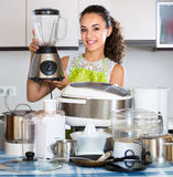 Positive housewife with blender and kitchenware Stock Photo