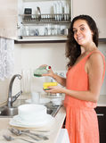 Positive housewife cleaning dirty dishes in home Royalty Free Stock Photos