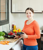 Positive housewife cooking eggplants in home Stock Image