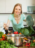 Positive housewife cooking fresh vegetables Royalty Free Stock Photography