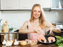 Positive housewife cooking raw salmon Royalty Free Stock Image