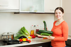 Positive housewife cooking with squash Royalty Free Stock Photos