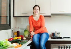 Positive  housewife  in home kitchen Royalty Free Stock Photography