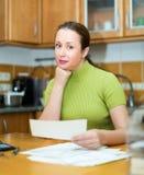 Positive housewife looking through bills Stock Photo