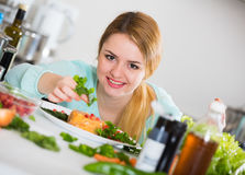 Positive housewife with plate of salad in kitchen. Young woman with plate of vegetable salad and cheese indoors Royalty Free Stock Image