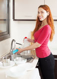Positive housewife washing plates with sponge Stock Image