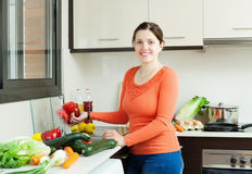 Positive housewife washing  vegetables Royalty Free Stock Photography