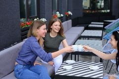 Positive housewives meeting at cafe and drinking coffee. Concept of free time and gossips Stock Images