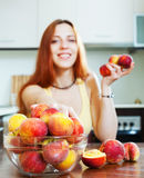 Positive houswife with peaches Stock Photography