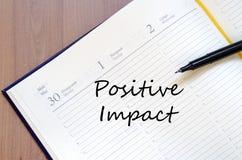 Positive impact write on notebook Stock Photo