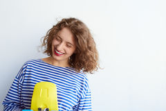 Positive indoor portrait of hipster woman having fun. Happy emotions, trendy striped clothes, curly hair, positive mood, white wall bright colors. holding Royalty Free Stock Photo