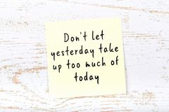 Positive inspiring quote handwritten on sticky note on wooden background stock photo
