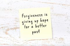 Positive inspiring quote handwritten on sticky note on wooden background stock image