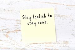 Positive inspiring quote handwritten on sticky note on wooden background royalty free stock photo