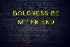 Positive inspiring quote on neon sign against brick wall boldness be my friend stock photos