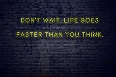 Positive inspiring quote on neon sign against brick wall dont wait life goes faster than you think stock illustration