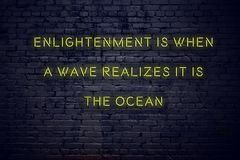 Positive inspiring quote on neon sign against brick wall enlightenment is when a wave realizes it is the ocean.  stock photos