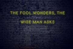 Positive inspiring quote on neon sign against brick wall the fool wonders the wise man asks royalty free stock images