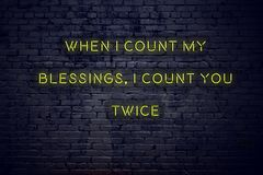 Positive inspiring quote on neon sign against brick wall when i count my blessings i count you twice royalty free illustration