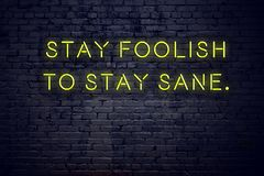 Positive inspiring quote on neon sign against brick wall stay foolish to stay sane.  royalty free illustration