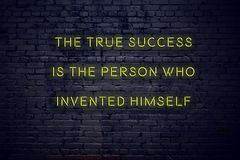 Positive inspiring quote on neon sign against brick wall the true success is the person who invented himself royalty free stock photo