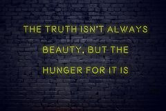 Positive inspiring quote on neon sign against brick wall the truth isnt always beauty but the hunger for it is royalty free stock photo