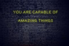 Positive inspiring quote on neon sign against brick wall you are capable of amazing things.  vector illustration
