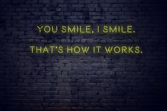 Positive inspiring quote on neon sign against brick wall you smile i smile thats how it works royalty free illustration