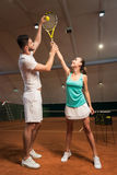 Positive instructor teaching to play tennis Royalty Free Stock Photos