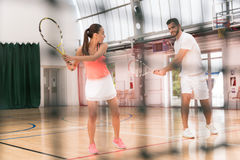 Positive instructor teaching to play tennis Stock Images