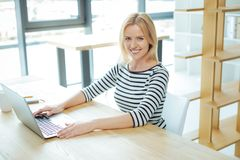 Positive intelligent woman sitting in front of the laptop. Ready to work. Positive intelligent pretty woman sitting in front of the laptop and smiling while Stock Photo