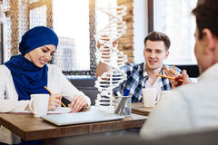 Positive international students studying genetics. Ready with our project work. Positive involved international students sitting at the table and learning stock images