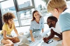 Positive internationale Studenten, die zusammen an dem Hochschulprojekt arbeiten Stockfotos