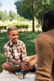 Positive joyful boy sitting on the plaid. On the grass. Positive joyful boy sitting on the plaid while listening to his father stock photo