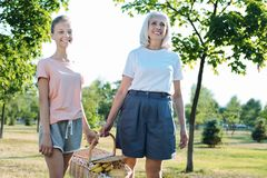 Positive joyful grandmother and granddaughter holding a basket. On a picnic. Positive joyful delighted grandmother and granddaughter holding a basket with food Royalty Free Stock Photo