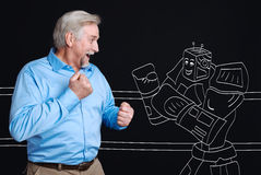 Positive joyful man fighting with a robot. Age of technology. Positive joyful aged man holding fists and standing apposite the robot while having a fight with Royalty Free Stock Photos