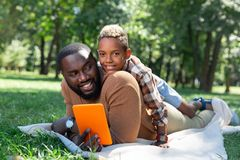 Positive joyful man holding a new tablet. Modern device. Positive joyful men holding a tablet while being together with his son royalty free stock photography