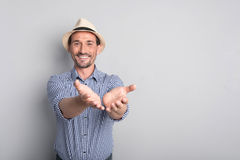 Positive joyful man pretending to give something. Helpful and generous. Nice delighted bearded man holding his hands in front of him and smiling while sharing Stock Photography