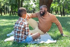 Positive joyful man speaking with his son. Pleasant conversations. Positive joyful men speaking with his son while sitting together with him royalty free stock photography