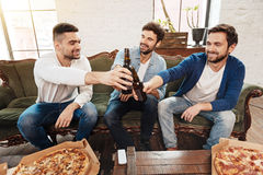 Positive joyful men raising beer bottles for toast. Cheers my friends. Positive joyful nice men sitting on the sofa and holding beer bottles while cheering with Stock Photography