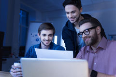 Positive joyful programmers enjoying working together. Friendly atmosphere. Positive nice joyful programmers looking at the document and smiling while enjoying Royalty Free Stock Photos