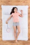 Positive junge Frau, die auf Bett liegt Stockbilder
