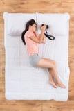 Positive junge Frau, die auf Bett schläft stockbild
