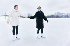 Positive junge Frauen auf Eisbahn lizenzfreies stockbild