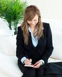 Positive junge Geschäftsfrau, die zu Hause Kenntnisse nimmt Stockbild
