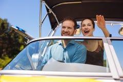 Positive junge Paare, die Spaß während Segelboot haben Stockfotos