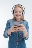 Positive junge weibliche Person, die ihr Telefon betrachtet Lizenzfreie Stockbilder
